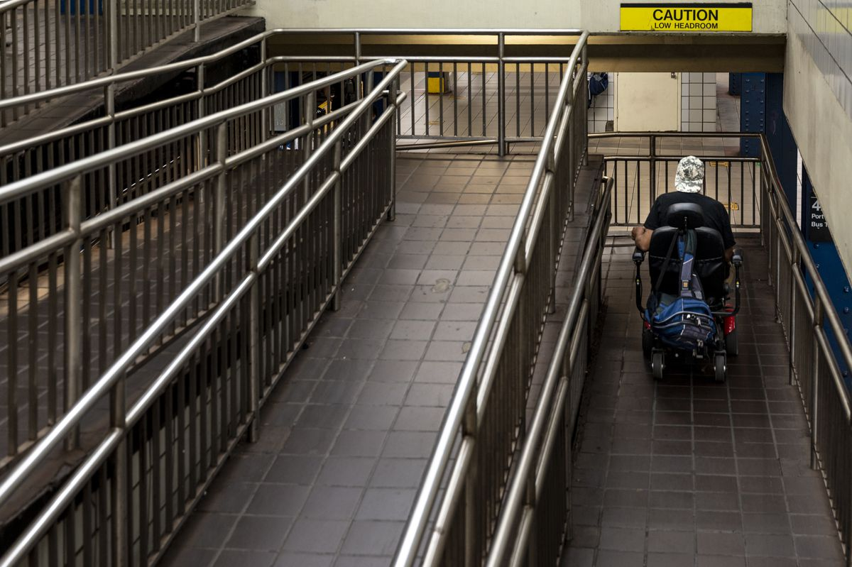 A wheelchair user takes a ramp down to the A trains platform at W 42st and Port Authority.