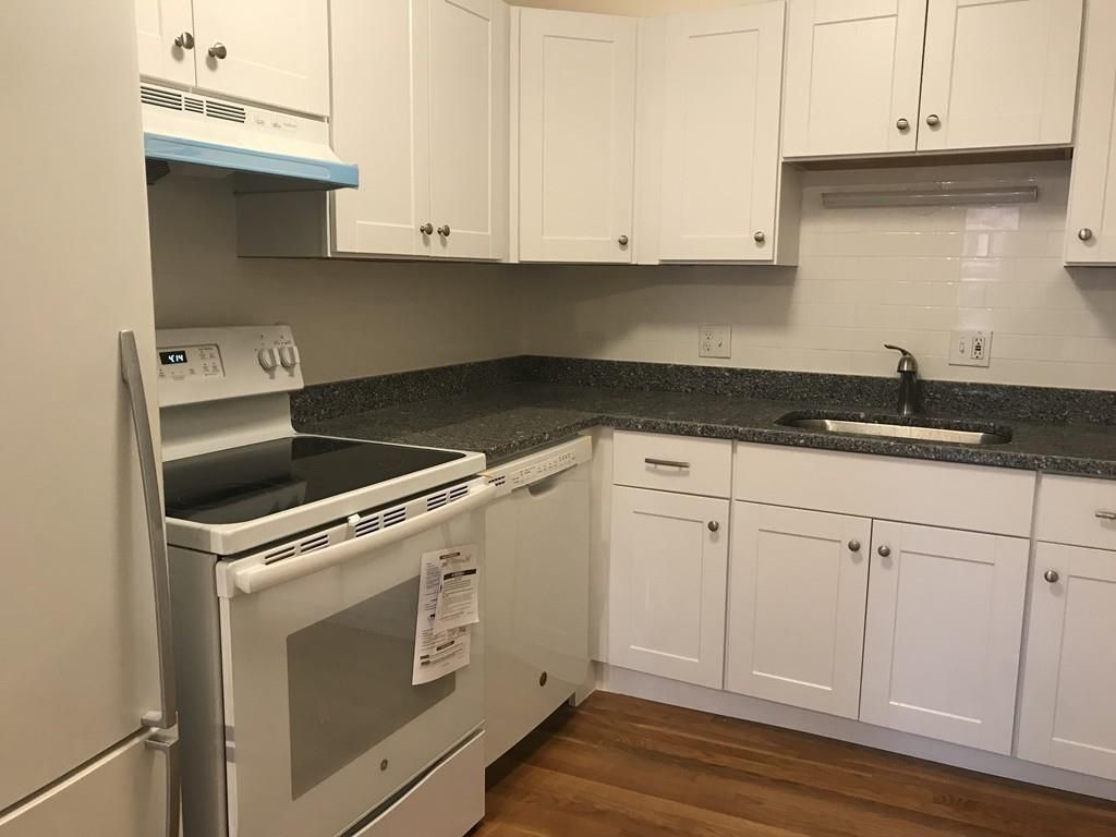 The kitchen, which has an L-shaped counter and a brand-new stove.