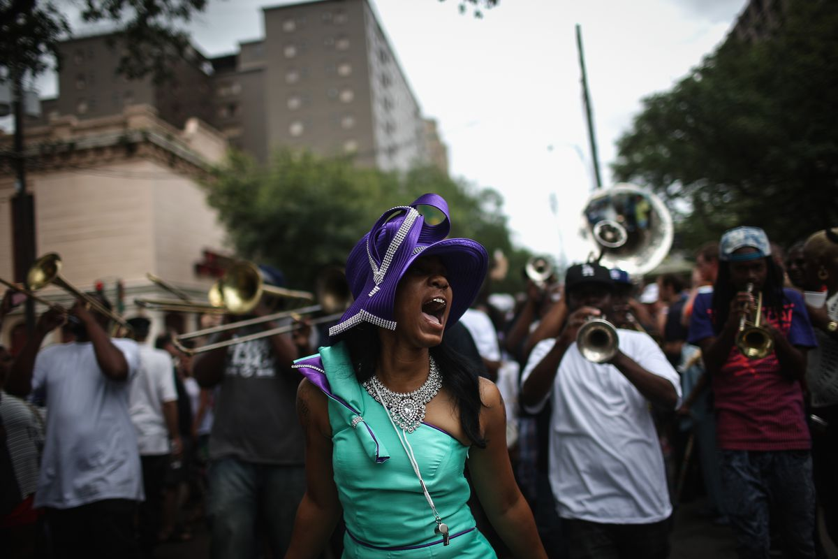 A woman wearing an elaborate purple hat cries out in front of a brass band in an urban setting