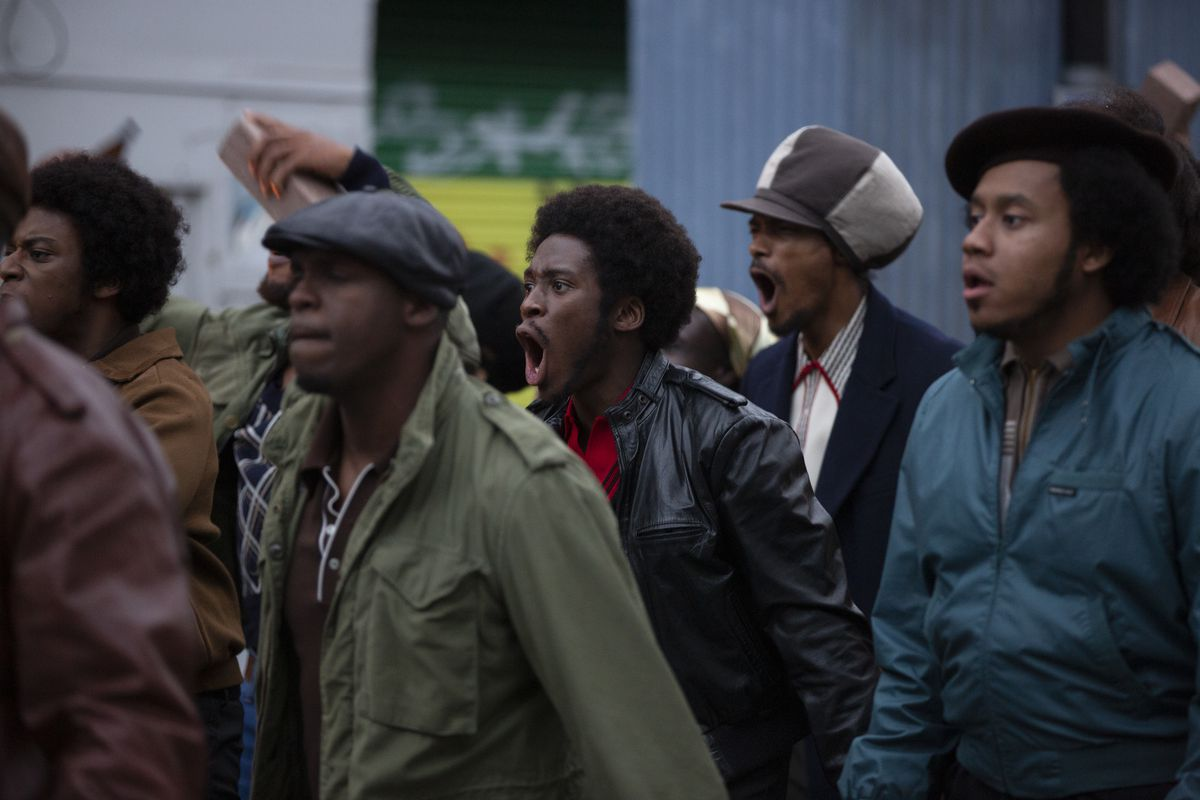 A group of men stand in a crowd, shouting.