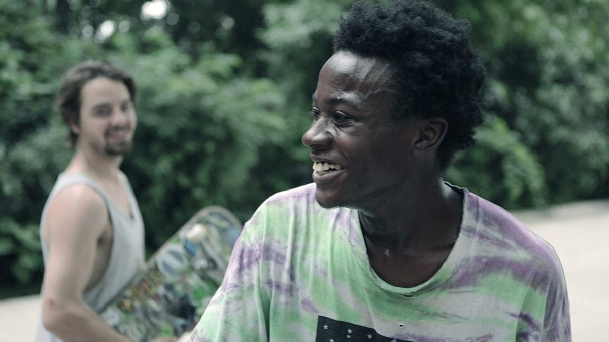 a young black man smiles while his friend holds a skateboard in the background in minding the gap