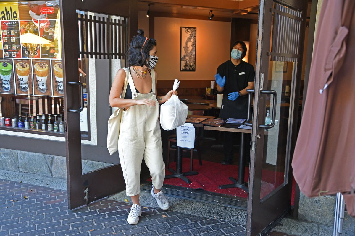 A customer wearing a protective mask receives a takeaway meal from a restaurant during the coronavirus pandemic on May 20, 2020.