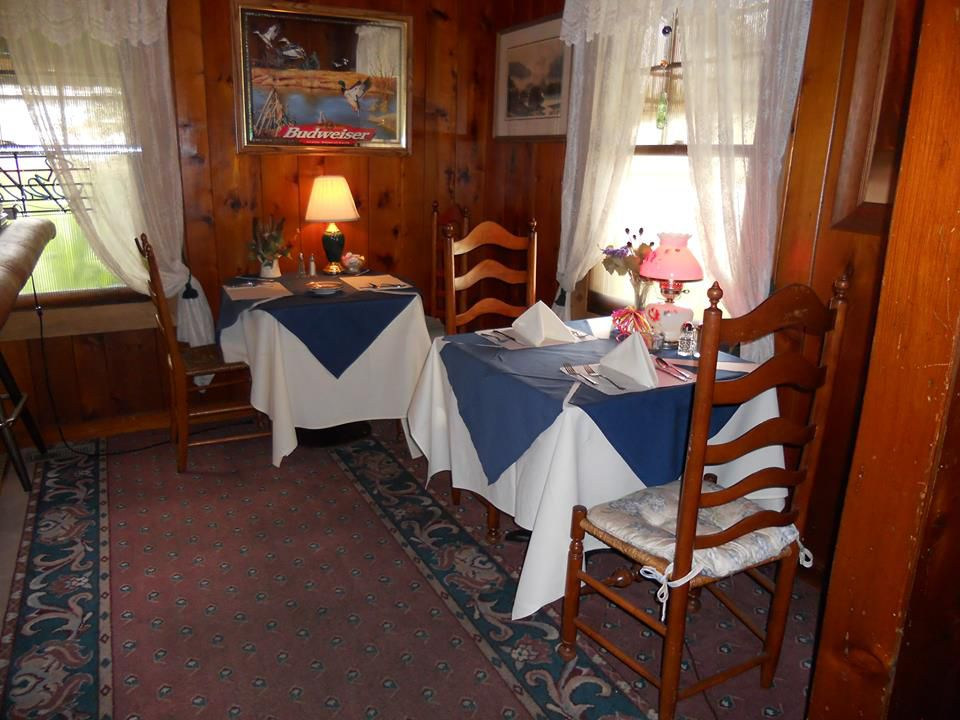 The interior of Dupuis Restaurant in Port Angeles, WA, with two small tables, white curtains, an ornate rug, and wood walls with vintage decor