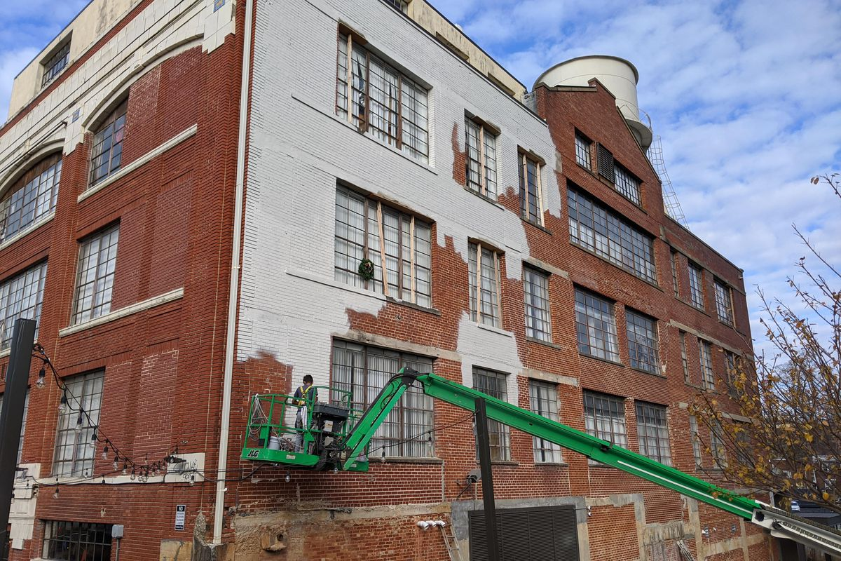 Crews, using a green cherry-picker, are painting the old red brick white.