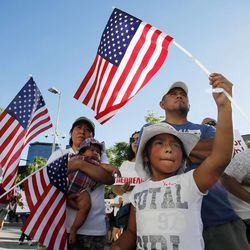 Yatziri Gaytan waves a flag during a prayer vigil in Salt Lake City, Thursday, June 27, 2013. Behind her are her parents, Rolando and Angelica and her sister Yaritza.