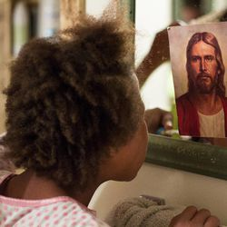 """Emma, 11, looks at a picture of Jesus while brushing her teeth in the bathroom. Some of her favorite things are the movie """"Frozen"""" and the temple."""