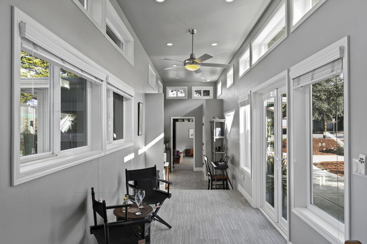 A long hallway with gray walls and white trim and lots of windows.