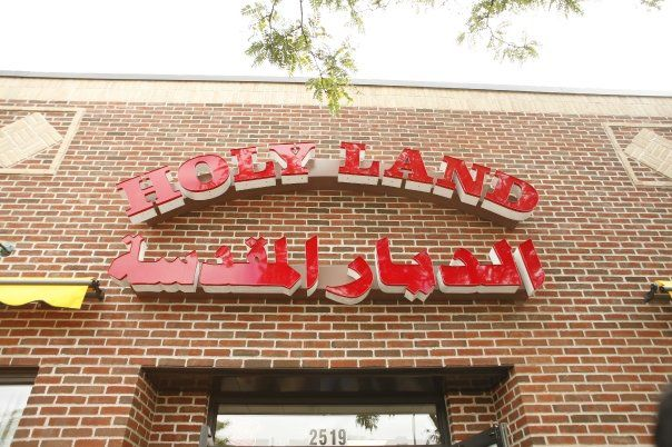 The red brick exterior and red lettered sign of Holy Land