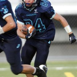 Juan Diego's David Alexander runs with the ball after intercepting a pass in the last seconds of the first half of a football game at Juan Diego High School in Draper on Friday, Sept. 7, 2012.