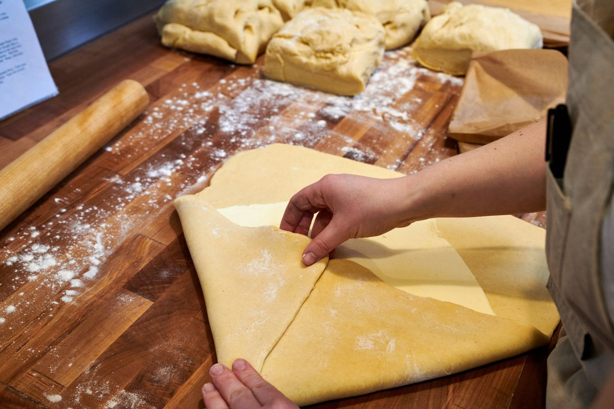 Herbert Suda's hands pinch two corners of pastry as they meet at the center of a square of butter. The rolled square of butter sits within the diamond of rolled brioche dough, to be folded around the butter like an envelope.