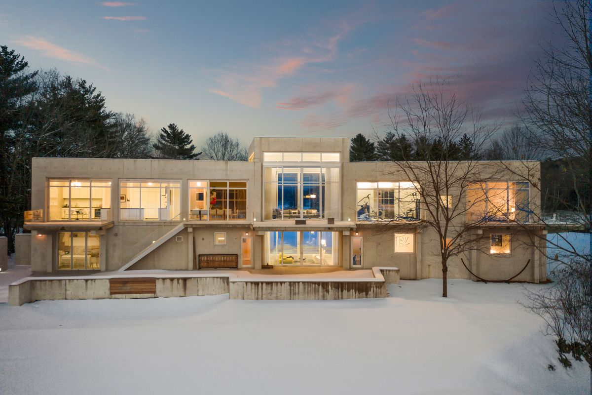 An all-concrete home with large windows sits on a snowy landscape at dusk. The home's windows are lit up.