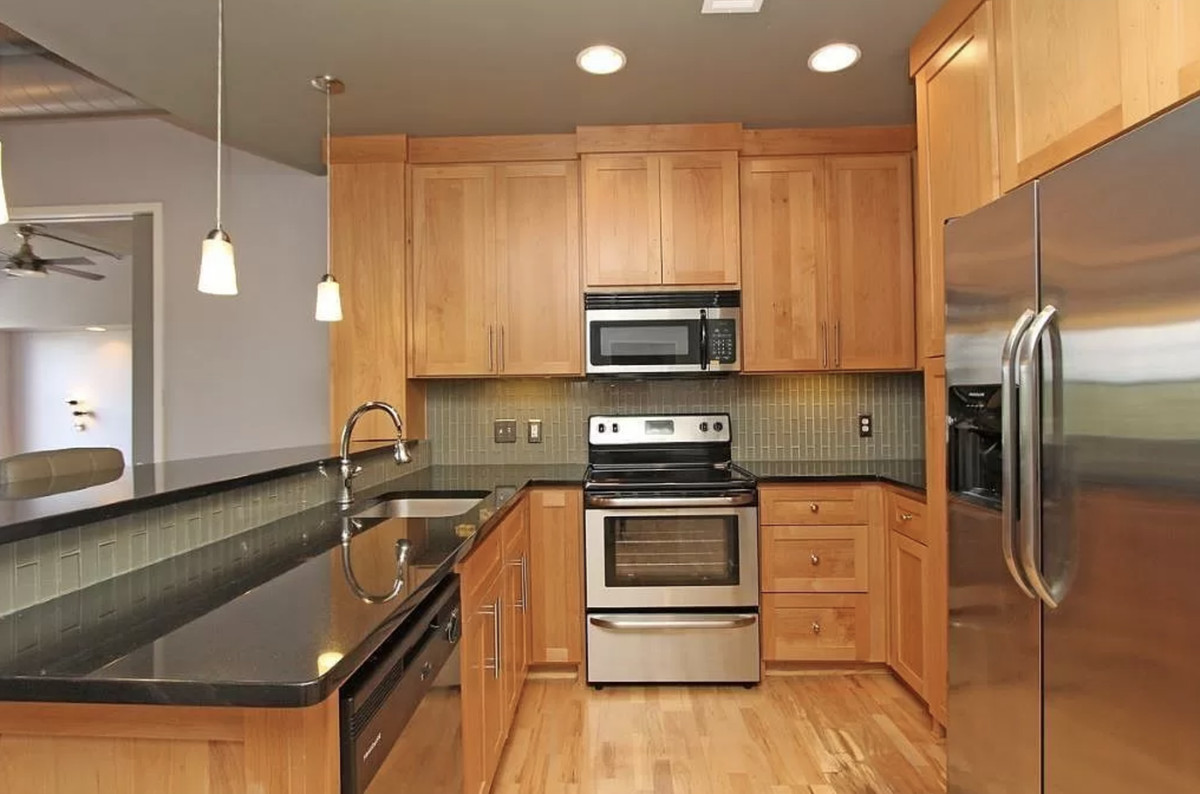 Kitchen with wood cabinets, black countertops and stainless appliances.