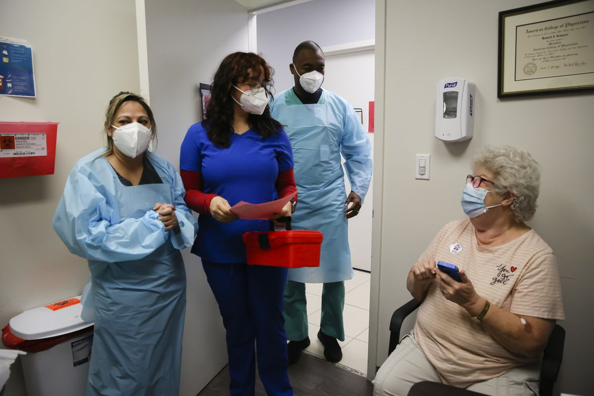 Health care workers stand in the doorway of an examination room where a person sits waiting for them to administer a shot.
