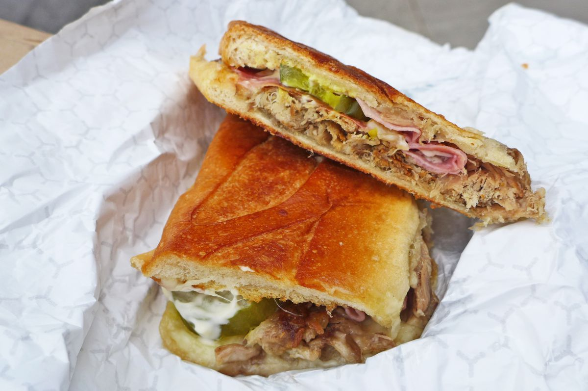 A sandwich pressed flat with pork, ham, and green pickle chip visible inside.