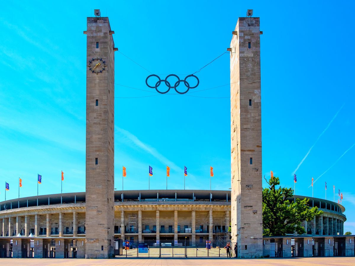 The exterior of the Olympiastadion Berlin. There are two tall structures in front where the Olympic symbol is suspended on a string.