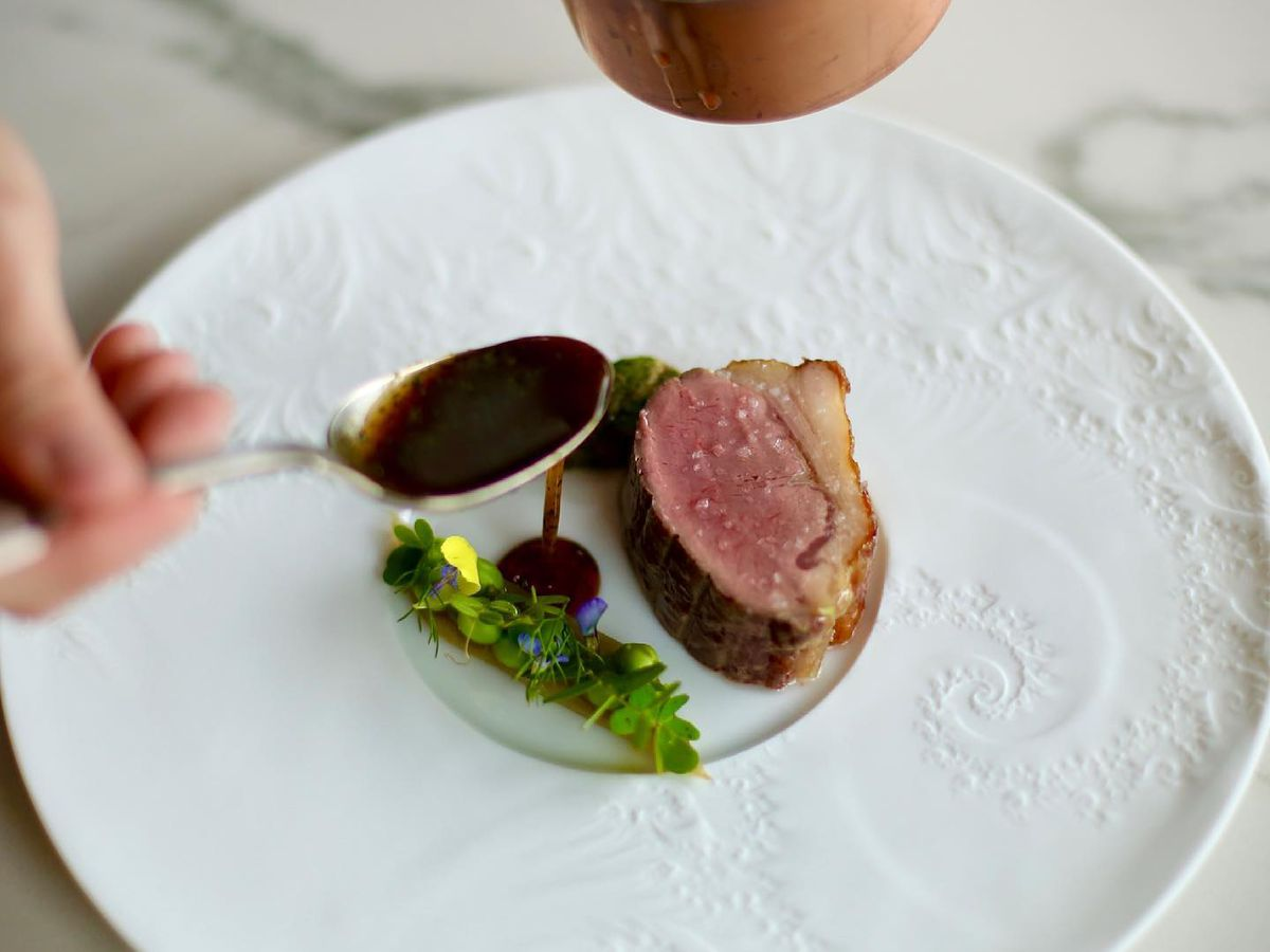 A roasted saddle of lamb and sweetbread with celery and English peas.