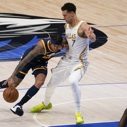 Utah Jazz guard Jordan Clarkson, left, attempts to get past the defense of Dallas Mavericks center Dwight Powell (7) in the first half of an NBA basketball game in Dallas, Monday April 5, 2021.
