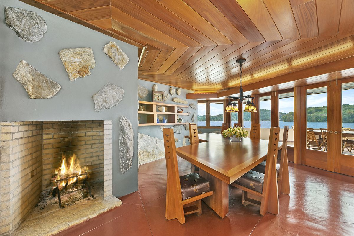 A dining area with a fireplace, table, chairs, and a wooden ceiling. There are tall windows overlooking a body of water.