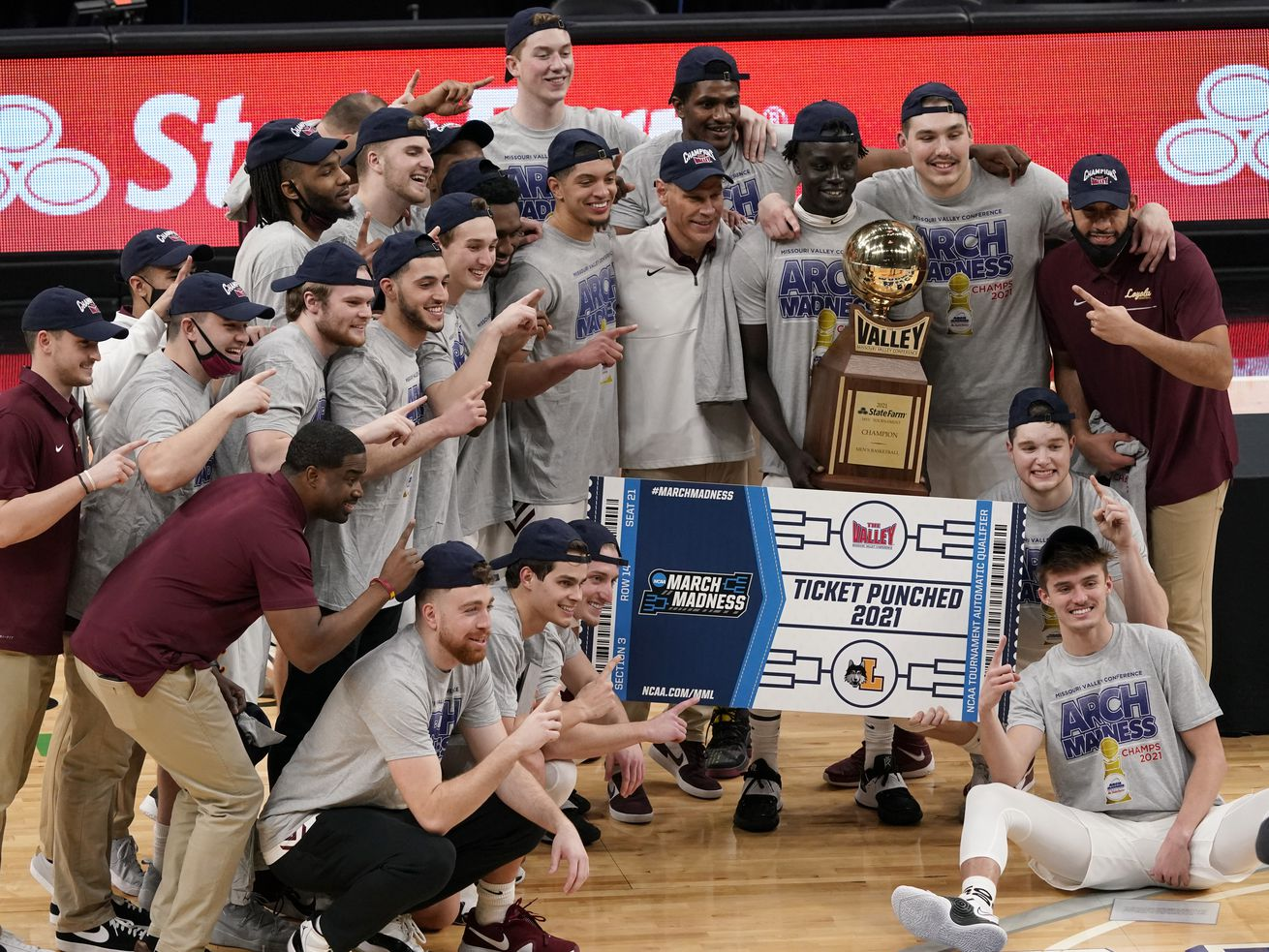 Loyola players and coaches celebrate after winning the Missouri Valley Conference championship.