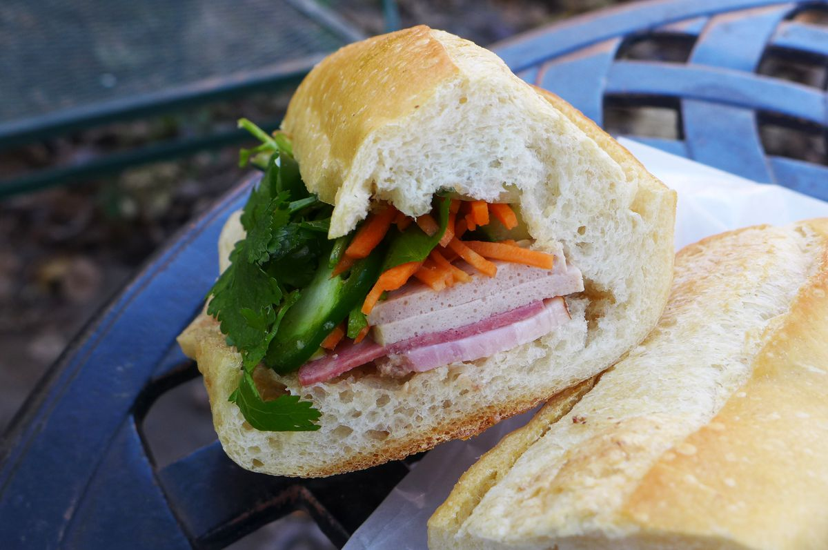 A sandwich on a baguette layered with several types of meat, plus cilantro and shredded carrots.
