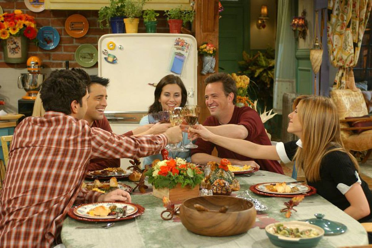 """The cast of """"Friends"""" siting at a dinner table leaning in and clinking their glasses in a toast."""