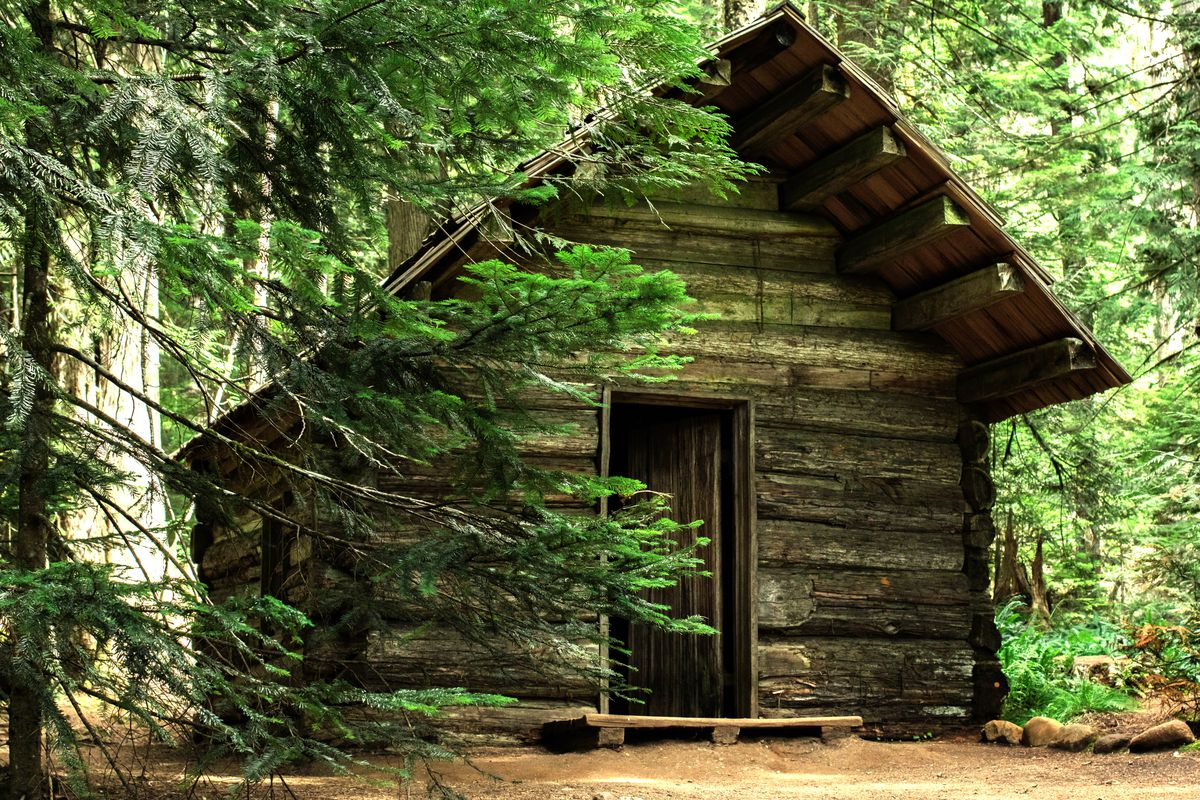 A cabin in the woods. The cabin is made of wood and has a sloped roof.