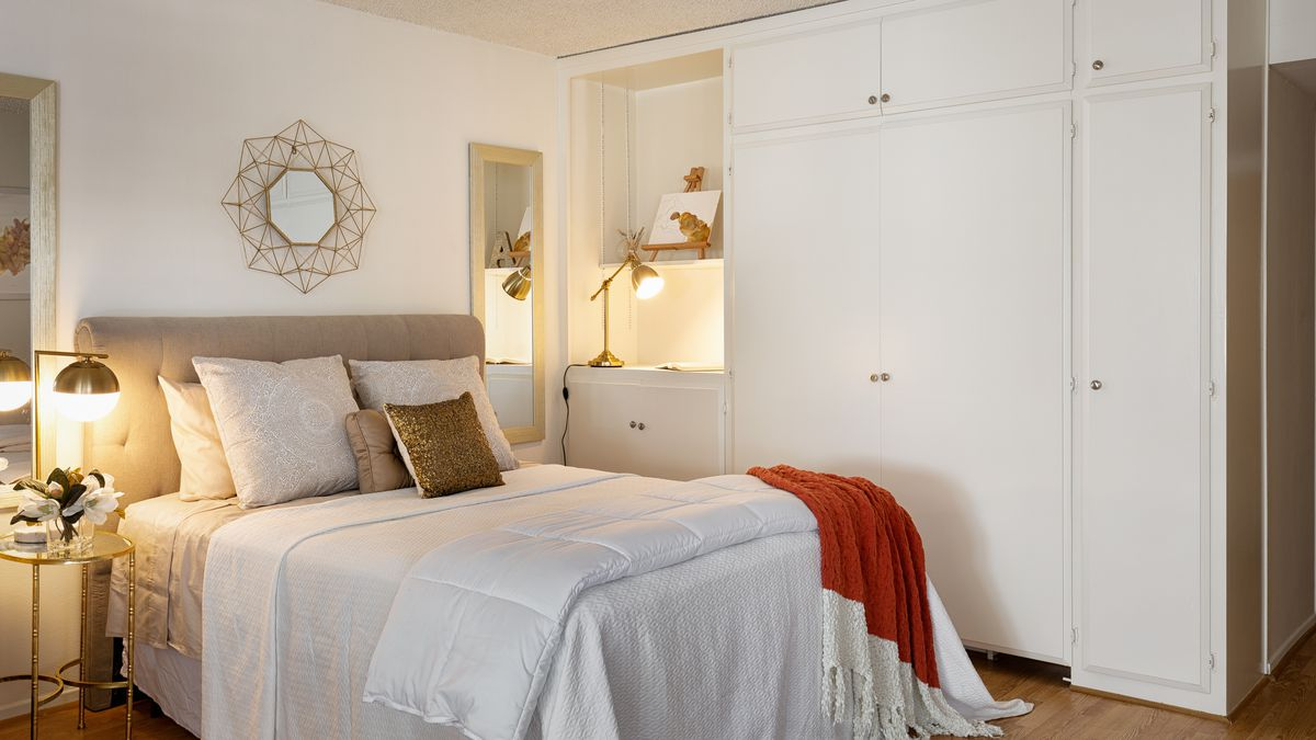 A small bed with a night lamp on one side and closets on the other