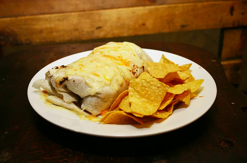 A large burrito and tortilla chips are served on a white plate on a wooden surface