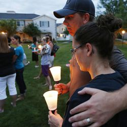 Steve and Cyndi Ford hug as friends gather during a candle light vigil in Logan Thursday, July 10, 2014. Ronald Lee Haskell, a recent Logan resident, has been charged with multiple counts of capital murder in a shooting in Texas. Haskell and his family lived in Logan for several years.