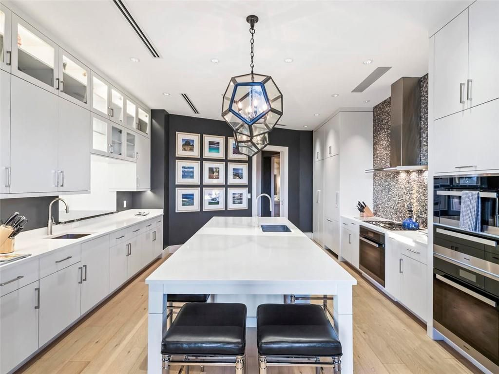 A white and blue kitchen with a huge pending lights in the middle.