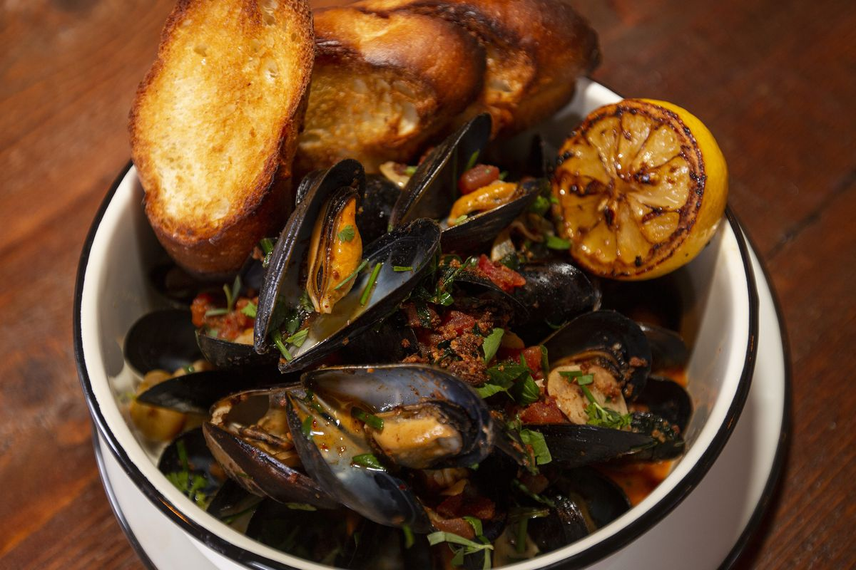A white bowl of cooked mussels