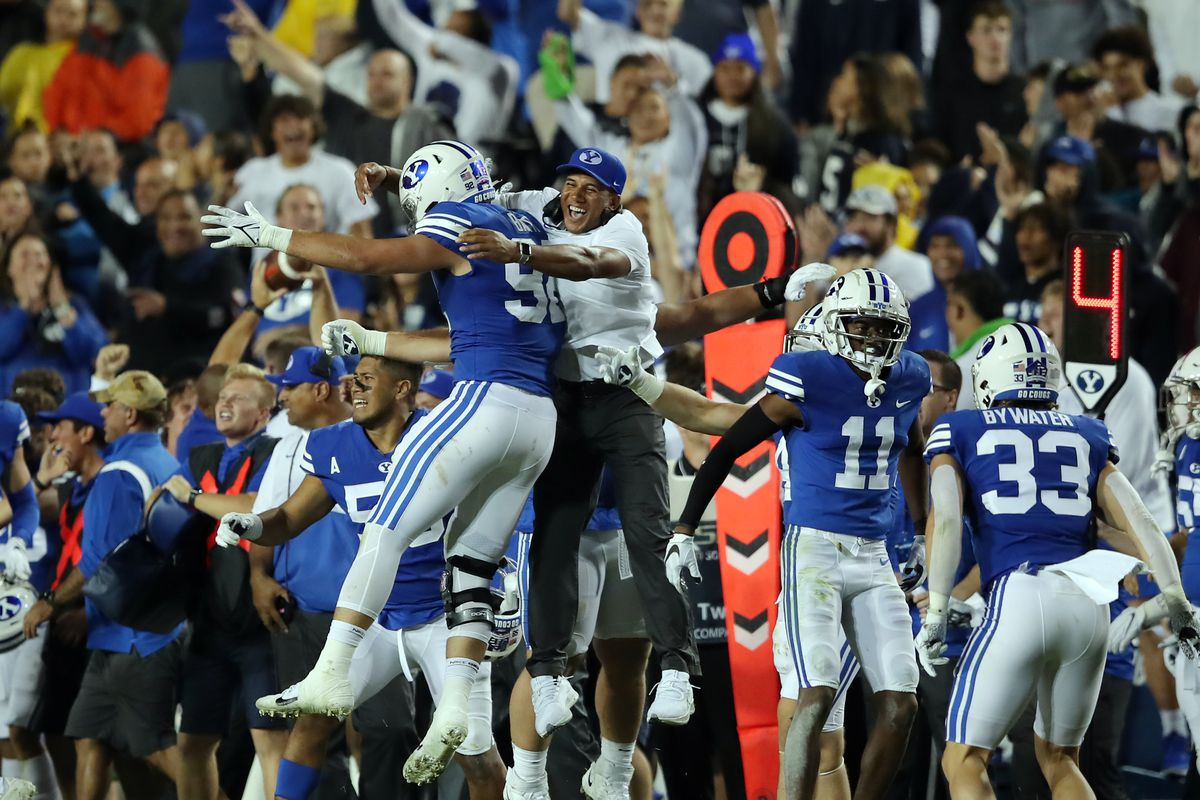 BYU players and coaches begin celebrating as they defeat Utah in an NCAA football game at LaVell Edwards Stadium in Provo on Saturday, Sept. 11, 2021. BYU won 26-17, ending a nine-game losing streak to the Utes.