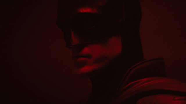 close-up of Robert Pattinson as Batman in a dark red room in The Batman