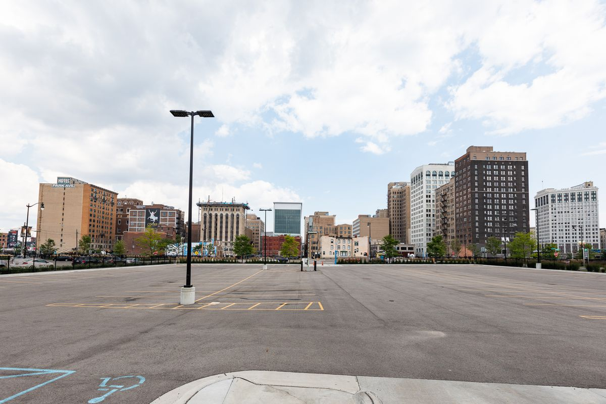 A huge surface parking lot. Many buildings stand in the distance.