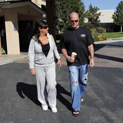 Jim McMahon and his girlfriend, Laurie Navon, walk to their car following an interview in Layton on Oct. 1.