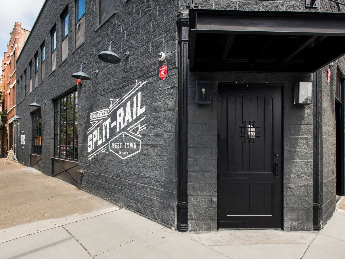 A black-painted brick building with an awning at the entrance.