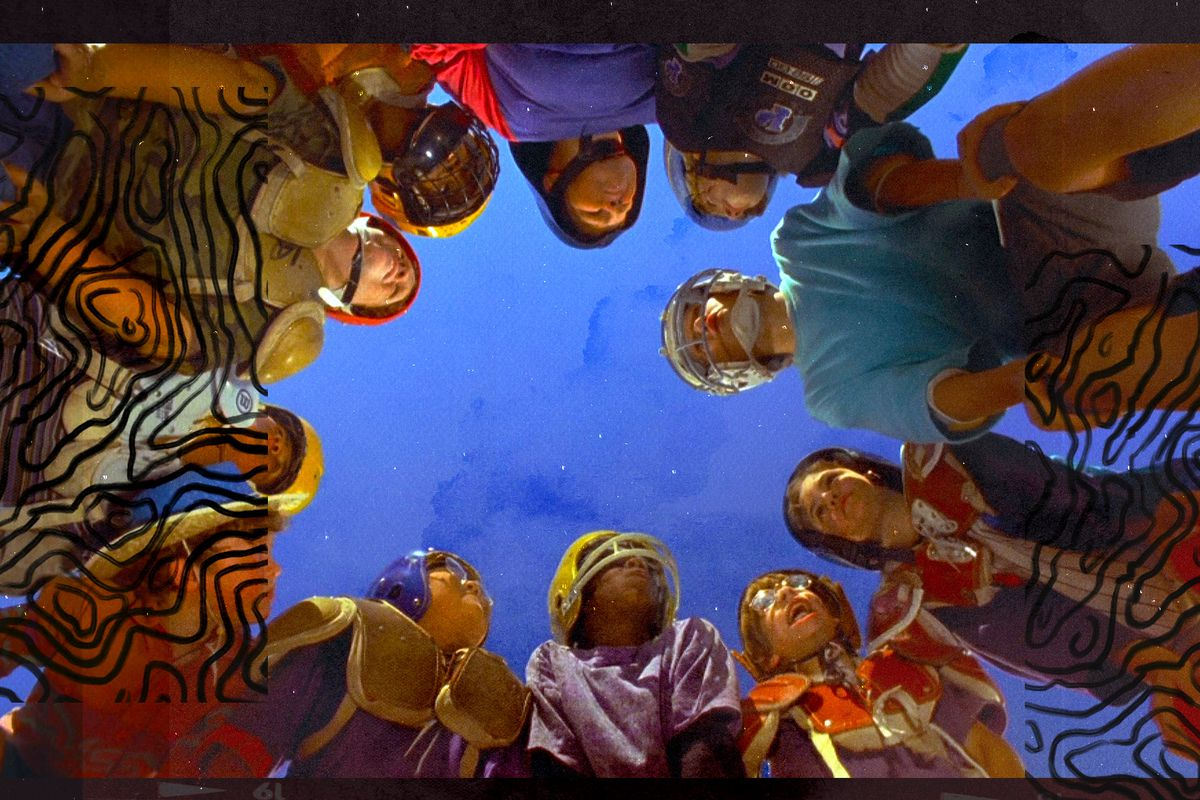 """A still from the movie """"Little Giants"""" of the team in a huddle, looking down at the camera"""