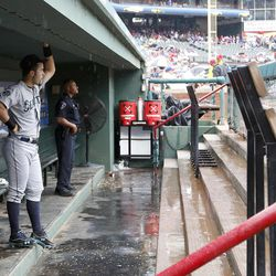 Seattle Mariners' Jesus Montero looks on from the dugout as rain falls during a weather delay before a baseball game against the Texas Rangers on Sunday, Sep. 16, 2012, in Arlington, Texas.