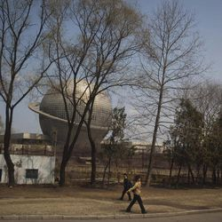 North Korean residents pass by a planetarium at the Three Revolutions Exhibition Hall in Pyongyang Wednesday, April 11, 2012. North Korean space officials have said that all assembly and preparations for a planned satellite launch have been completed, while denying it is a cover for missile test.