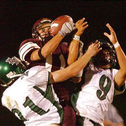 Jordan's Mark Lochhead, center, is sandwiched between Hillcrest's Kurt Nacey, left, and Sefesi Sitake during the Huskies' convincing win on Friday night.