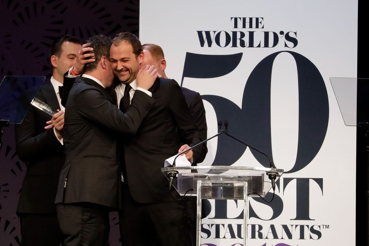 Will Guidara and Daniel Humm embrace on stage in front of a World's 50 Best Restaurants banner.