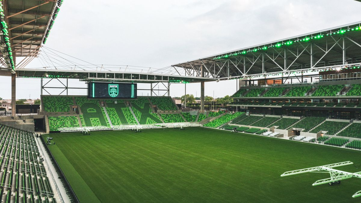 """A green soccer field with green stadium seats, including a section that reads """"ATX"""""""