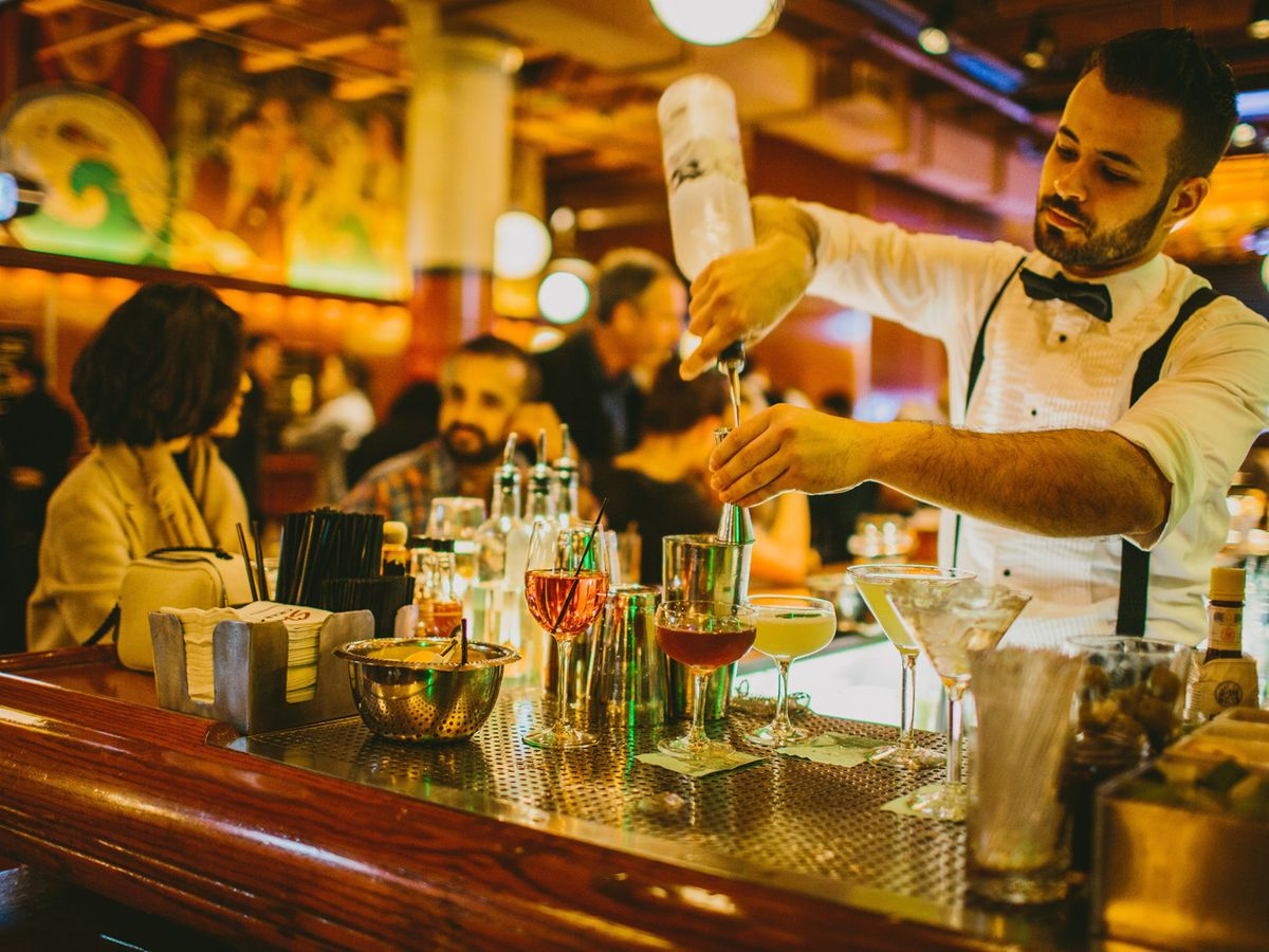 A bartender with a bowtie and suspenders mixes classic drinks.