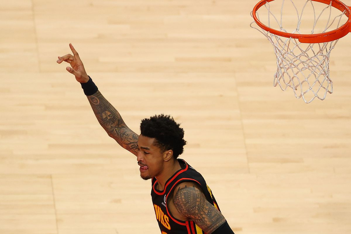 John Collins of the Atlanta Hawks reacts after a dunk against the Denver Nuggets during the second half at State Farm Arena on February 21, 2021 in Atlanta, Georgia.