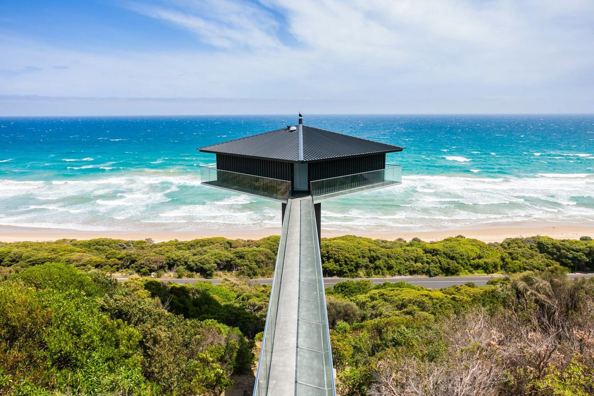 Home that appears to float in ocean right off the beach accessed by a long ramp.