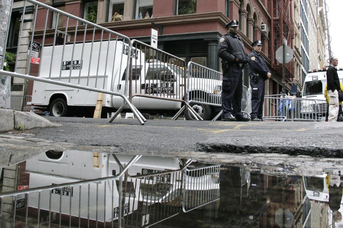 New York City policemen stand at a barricade on Monday, April 23, 2012 in the SoHo neighborhood in the borough of Manhattan in New York. Authorities have resumed digging up the basement of the building in the background in connection with the disappearanc