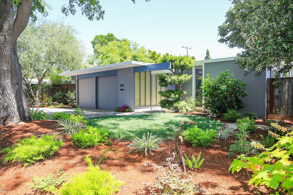 Exterior front of Eichler with blue trim and gray facade.