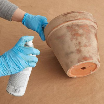 Person Sprays Outside Of Terra Cotta Pot With Matte Sealer Spray