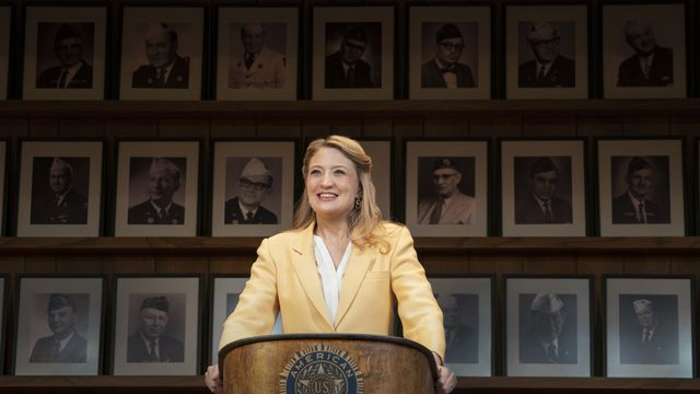 a woman stands at a podium