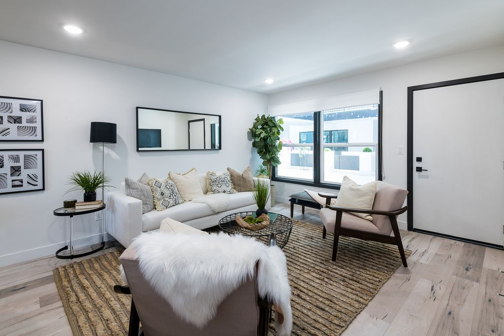 A room with gray floors and white walls, furnished with a white sofa and a pair of small armchairs